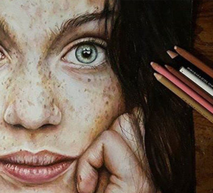Colored pencils next to a portrait drawing